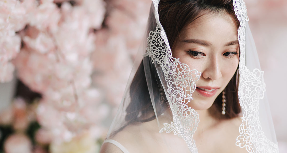 bride poses with veil over face in front of cherry blossom tree