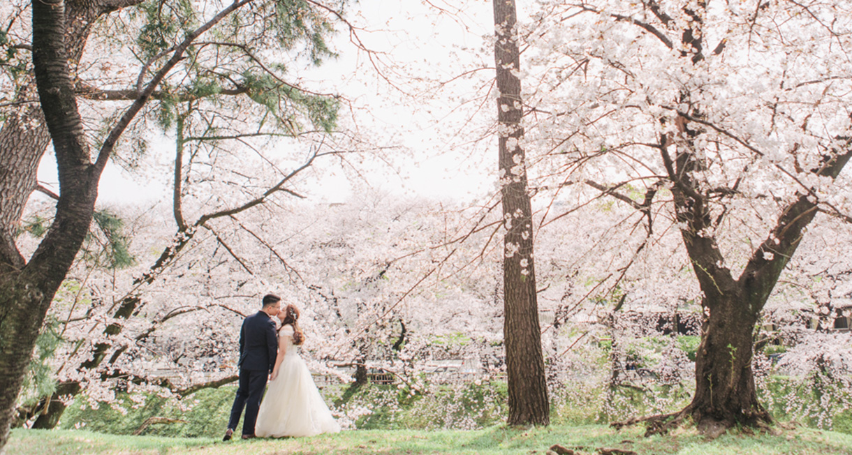 couple pose with surrounding spring blossom