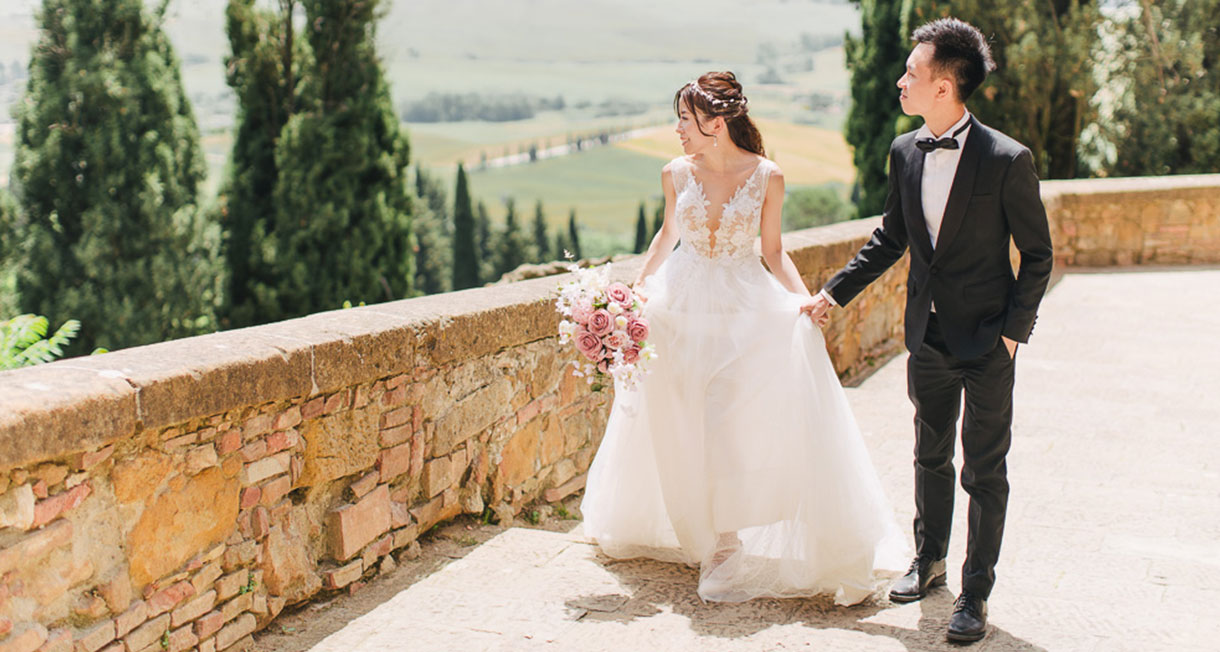 bride and groom walk through rustic street in tuscany