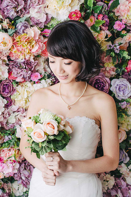 asian bride poses next to floral backdrop