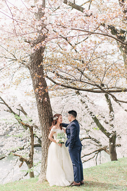 bride and groom in cherry blossom trees