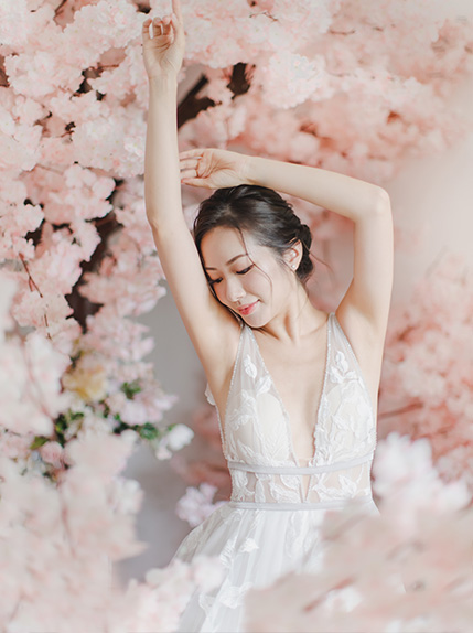 bride lifts arms in air during photoshoot by cherry blossom
