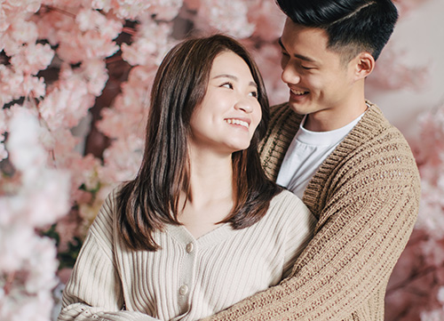 couple poses in front of pink cherry blossom