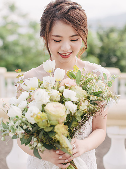 bride smiles while looking at wedding bouquet