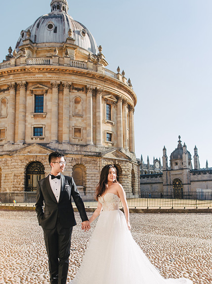 bride and groom pose in front of radcliffe camera