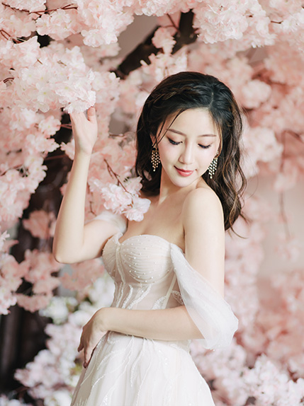 bride looks towards wedding dress while leaning on cherry blossom tree