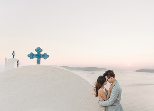 couple pose with greek santorini spire visible