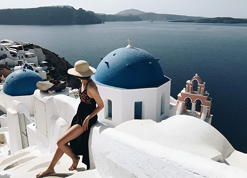 bride sits on wall with view of blue santorini water in the scene