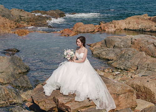 bride poses on rock with sea in background at shek o