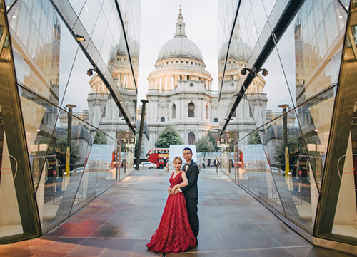 bride and groom pose with st pauls cathedral in the background