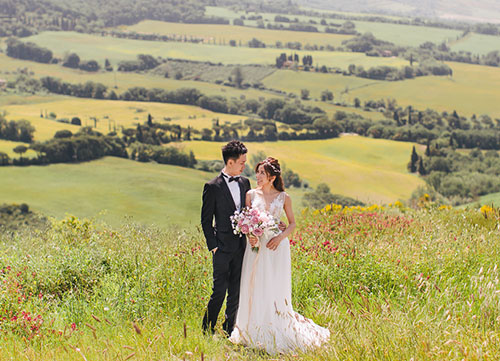 couple in wedding clothes posing in tuscan hills