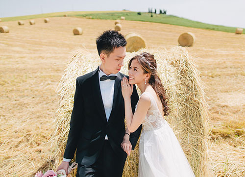 bride and groom stand in front of hay bale