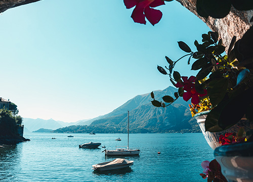 hidden view of lake como with boats a flowers