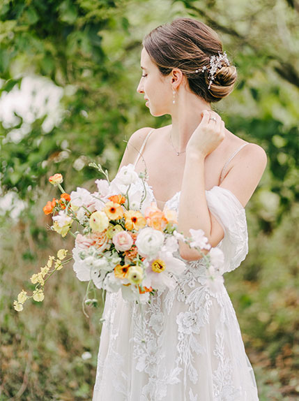 bride poses with bouquet surrounded by bushes