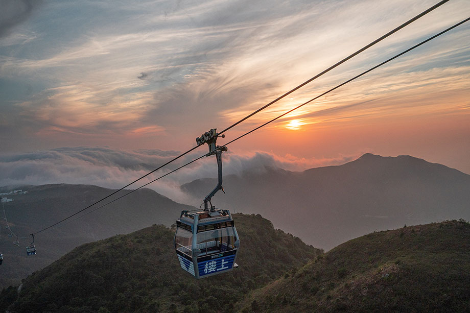 cable car on wires with hong kong hills in background