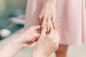 engagement rings being put onto brides finger