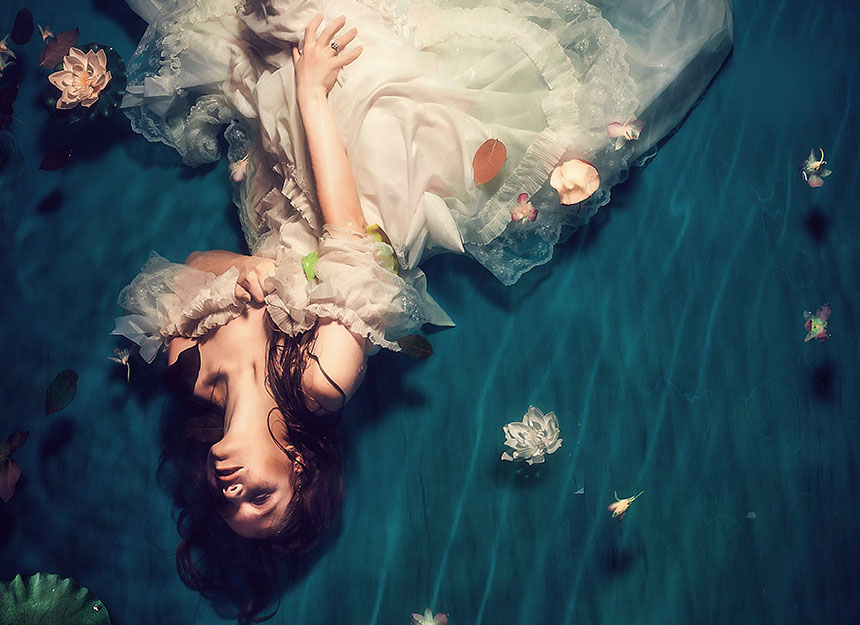 bride poses for pre wedding photoshoot under water
