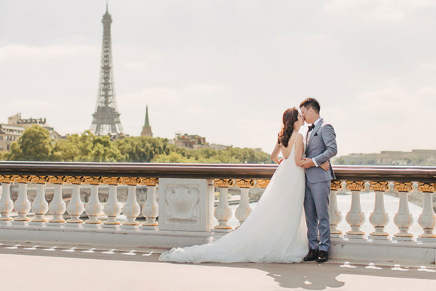 bride and groom pose in front of eiffel tower for pre wedding in europe