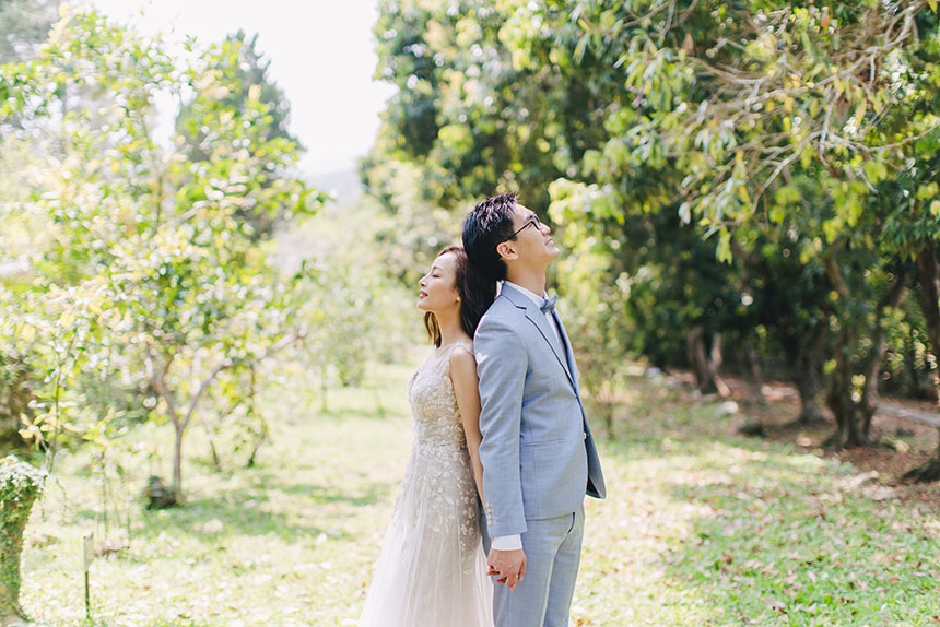 bride and groom pose back to back during engagement shoot