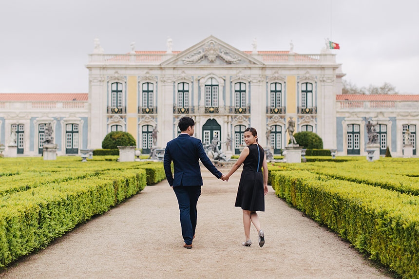 couple walk in front of historic lisbon building